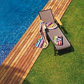 Lawn and wooden deck edging pool; brightly striped towels on modern sun lounger