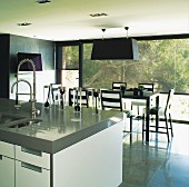 View across modern sink unit to cubic lamp above designer dining area; view of vegetation through continuous glass wall