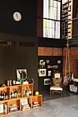 Double-height loft apartment with collection of spirits in crate-style shelving; gymnastic rings hanging form iron mezzanine balustrade and antique armchairs in corner