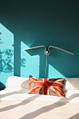 Union flag scatter cushion on double bed below seagull-shaped lamp on wall painted turquoise
