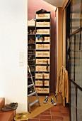 Schuh- und Kleidungsregal mit Schüben aus französischen Weinkisten in kleinem Lagerraum; Schuhe auf Treppenstufen mit Terracottafliesen im Vordergrund