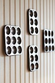 Four metal muffin trays of various sizes on light brown wooden wall