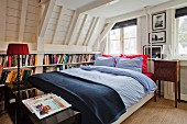 Bookcase built into knee wall of attic room behind double bed