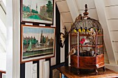 Antique, ornamental bird cage below white, wood-clad sloping ceiling next to historical cityscapes on wallpaper with wide stripes