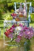 Blumenstrauss vor nostalgischem Metall-Gartentischchen gedeckt mit Früchten & Flaschen