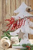 Tannenbaum aus Holz geschmückt mit Sternanhänger & Winterbeerenzweig (Ilex Verticillata)