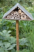 Insect hotel on wooden pole in flower bed