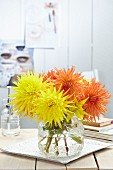 Orange and yellow fimbriata dahlias in glass vase