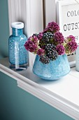 Allium flowers and ivy berries in vase