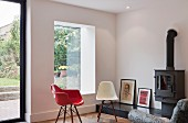 Classic chairs with red and white shell seats in front of wood-burning stove in minimalist living room with garden view