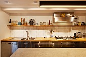 Kitchen counter with wooden worksurface, white-tiled splashback, extractor hood and wooden shelf