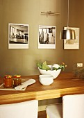 Wooden dining table in front of black and white photos on painted wall