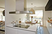 White kitchen counter with extractor hood in open-plan kitchen with dining area in background
