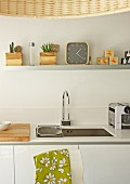 White kitchen counter with integrated sink below clock and potted plants on shelf