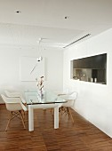 Dining area with designer glass table and classic Eames chairs; kitchen pass-through with roller shutter to one side