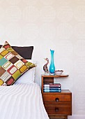 Retro-patterned scatter cushion on bed next to wooden bedside cabinet