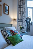 Colourful scatter cushions on bed in front of black and white patterned curtains