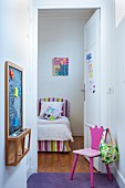 Pink child's chair opposite chalkboard in small anteroom with open door showing view of bed with striped headboard and valance