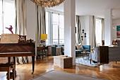 Offener Wohnraum mit antikem Klavier, hinter Stütze Loungebereich mit verschiedenen Sofas