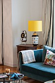 Blue sofa next to table lamp on antique table
