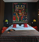 Colourful Oriental painting above double bed in bedroom painted dark brown