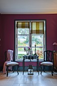 Two chairs and table in front of window with Roman blinds in purple wall
