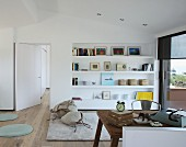Vintage desk and chair and pictures on shelves fitted in niche in study