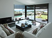 Sofas, coffee table and classic rocking chair in living room with sea view