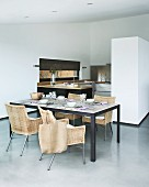 Set dining table and modern wicker chairs in purist interior; cabinet in partition wall and open-plan kitchen in background