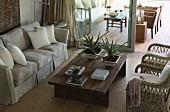 Pale couch and rattan armchairs around wooden coffee table adjoining terrace with open sliding door