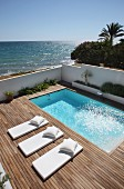 Pale futon sun loungers with matching pillows on wooden deck surrounding pool with ocean in background