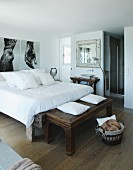 Rustic wooden bench at foot of double bed in bedroom with large photos on wall