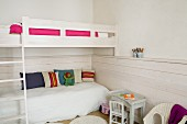 Bunk-beds with ladder, children's chair and table and wainscoting in white bedroom