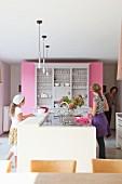 Moderne Küchentheke vor Vintage-Geschirrschrank an pinkfarbener Raumteilerwand, zwei Mädchen und Frau im Hintergrund