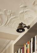 Antique-style wall lamp attached to bookcase in interior with floral, stucco ceiling
