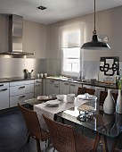 Retro pendant lamp above dining table made from glass table top on wooden trestles and wicker chairs in simple modern kitchen