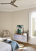 Painting of woman on vintage-style chest of drawers and antique chair at foot of double bed with blanket