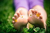 Little girl's toes decorated with daisies and buttercups and with drawn-on smiley faces