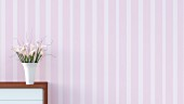Sideboard with vase of flowers against striped pink wallpaper