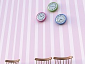 Three chair backrests below three wall clocks on striped wallpaper