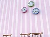 Three chair backrests below three wall clocks on striped wallpaper