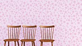 Three wooden chairs against lilac wallpaper with floral design