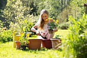 Smiling teenage girl repotting plants in the garden