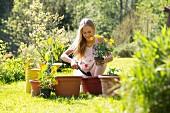 Lachendes Mädchen beim Umtopfen von blühenden Gartenpflanzen