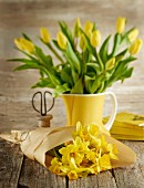 Yellow narcissus wrapped in paper and yellow tulips in ceramic jug