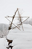 Star made from sticks on top of snow-covered woodpile
