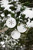 White Christmas baubles with snowflake motifs hanging from snow-covered fir branches