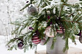 Spruce branches in old clay pot festively decorated with baubles and ribbons