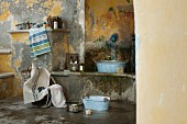 Waschbereich in Shabby Ambiente, Vintage Zinkwanne auf Steinbank unter Wasserspeier in französischem mediterranem Flair