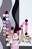 New-Year buffet with sparkling wine, sparklers and garlands of pastel circles decorating wall with grey and black pattern